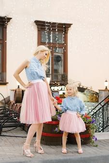 Blonde moeder en dochtertje in roze rokken en spijkeroverhemden houden hun handen buiten in de stad aan hun riem en kijken elkaar aan