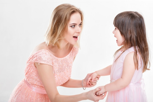 Blonde moeder troostende dochter in roze jurken prinsessen op grijze achtergrond. baby huilt