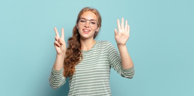 Blonde mooie en vrouw die vriendelijk glimlacht kijkt, nummer zeven of zevende met vooruit hand toont, aftellend