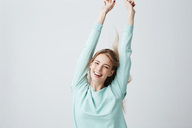 Blonde mooie jonge vrouw in het lichtblauwe bovenkant uitrekkende wapens omhoog in vrolijke stemming zoals het vieren van overwinning. breed glimlachend wijfje dat witte tanden en positieve emoties toont, die pret hebben binnen.