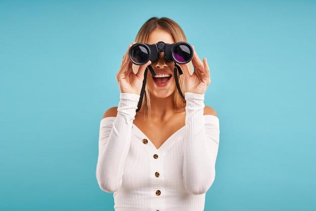 Blonde mooie volwassen vrouw poseren over blauw met een verrekijker