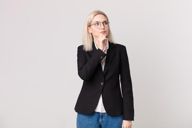 Blonde mooie vrouw denken, twijfelachtig en verward voelen. bedrijfsconcept Premium Foto