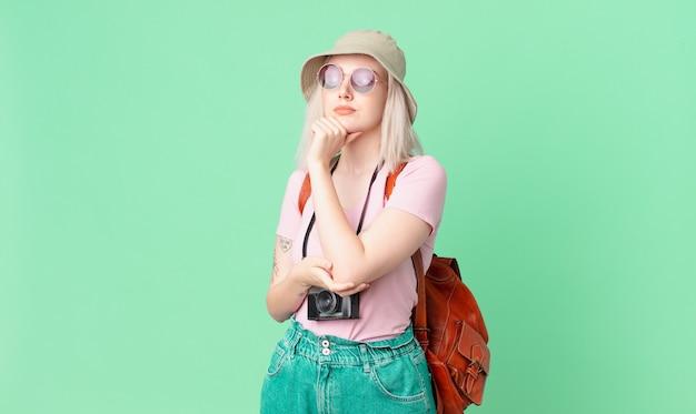 Blonde mooie vrouw denken, twijfelachtig en verward voelen. zomer concept