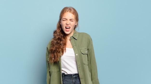 Blonde mooie vrouw die agressief schreeuwt, erg boos, gefrustreerd, verontwaardigd of geïrriteerd kijkt, nee schreeuwt