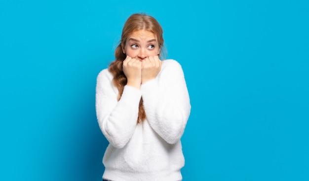 Blonde mooie vrouw die bezorgd, angstig, gestrest en bang kijkt, vingernagels bijt en op zoek is naar zijdelingse kopieerruimte
