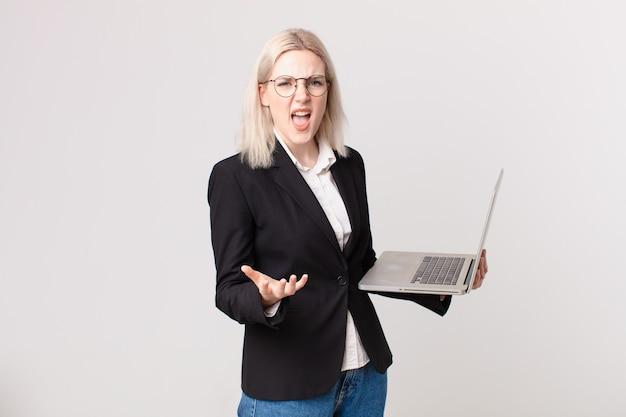 Blonde mooie vrouw die boos, geïrriteerd en gefrustreerd kijkt en een laptop vasthoudt