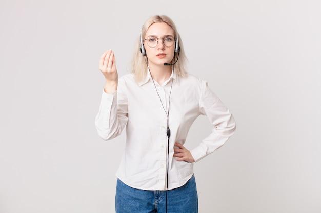 Blonde mooie vrouw die capice of geldgebaar maakt en u vertelt om telemarketingconcept te betalen