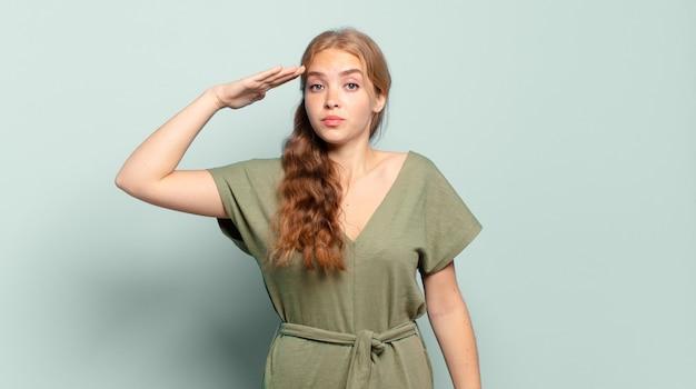 Blonde mooie vrouw die de camera begroet met een militaire groet in een daad van eer en patriottisme en respect toont