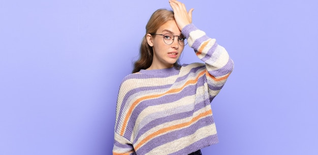 Blonde mooie vrouw die de handpalm naar het voorhoofd opheft, denkend oeps, na het maken van een domme fout of het herinneren, zich dom voelen