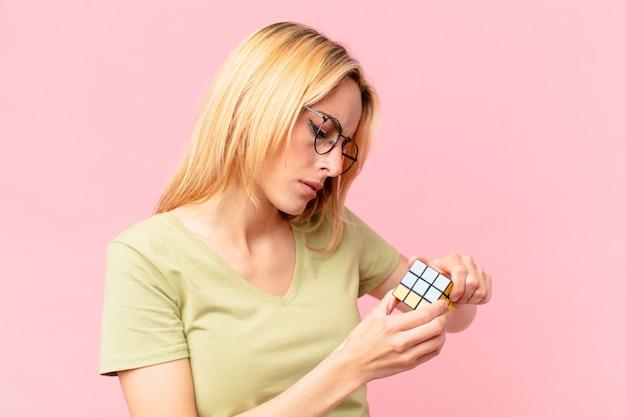 Blonde mooie vrouw die een logisch uitdagingsspel oplost