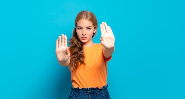 Blonde mooie vrouw die er serieus, ongelukkig, boos en ontevreden uitziet en de toegang verbiedt of stop zegt met beide open handpalmen