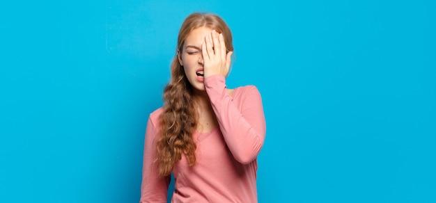 Blonde mooie vrouw die er slaperig, verveeld en geeuwend uitziet, met hoofdpijn en één hand die het halve gezicht bedekt