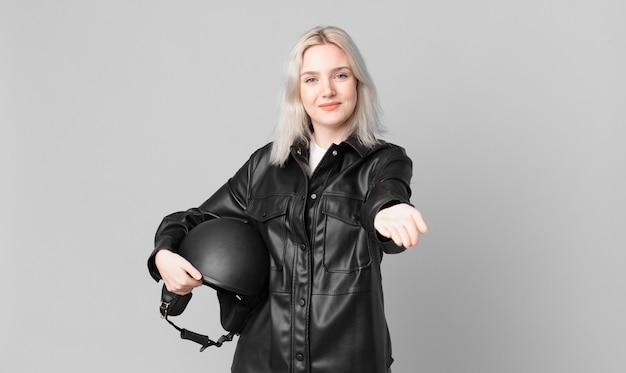 Blonde mooie vrouw die gelukkig glimlacht met vriendelijk en een concept aanbiedt en toont. motorrijder concept