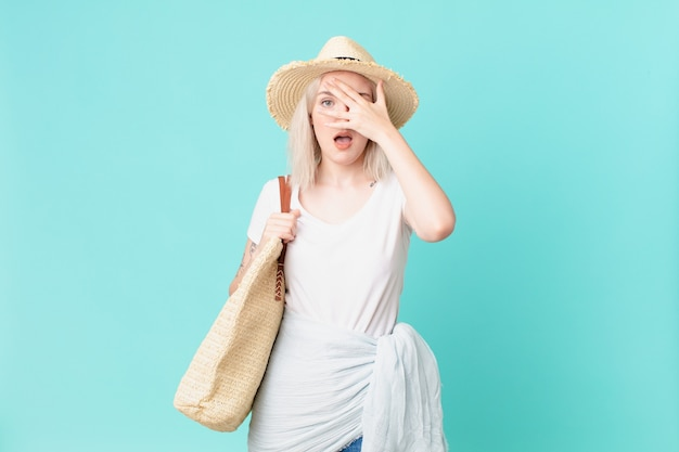 Blonde mooie vrouw die geschokt, bang of doodsbang kijkt en haar gezicht bedekt met de hand. zomer concept
