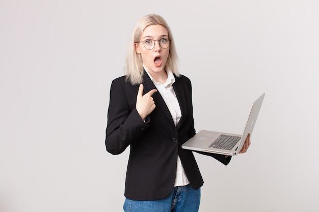 Blonde mooie vrouw die geschokt en verrast kijkt met de mond wijd open, naar zichzelf wijst en een laptop vasthoudt