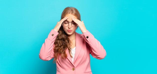 Blonde, mooie vrouw die gestrest en gefrustreerd kijkt, onder druk werkt met hoofdpijn en last heeft van problemen