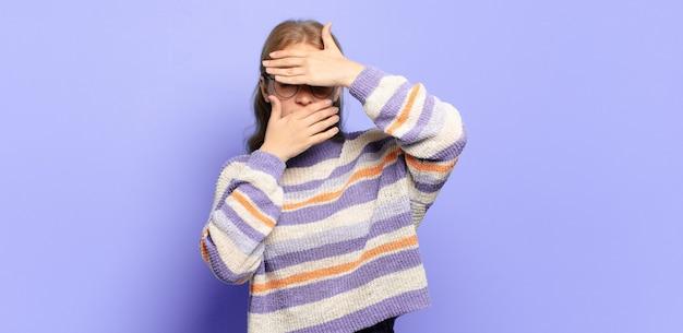 Blonde mooie vrouw die gezicht bedekt met beide handen en zegt nee tegen de camera! afbeeldingen weigeren of foto's verbieden