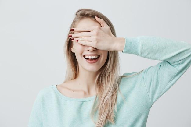 Blonde mooie vrouw die haar ogen met hand sluit, die gelukkige uitdrukking heeft, die breed glimlacht