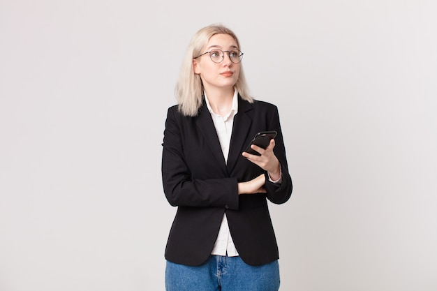 Blonde mooie vrouw die haar schouders ophaalt, zich verward en onzeker voelt en een mobiele telefoon vasthoudt