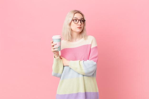 Blonde mooie vrouw die haar schouders ophaalt, zich verward en onzeker voelt. koffie concept