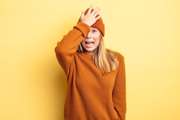 Blonde mooie vrouw die handpalm naar voorhoofd steekt en denkt oeps, na een domme fout te hebben gemaakt of zich dom te voelen