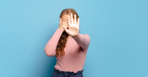 Blonde mooie vrouw die het gezicht bedekt met de hand en de andere hand naar voren steekt om de camera te stoppen, foto's of afbeeldingen te weigeren