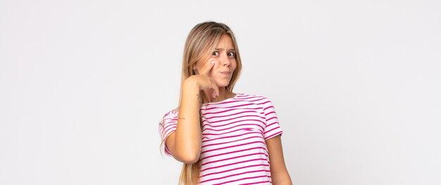 Blonde mooie vrouw die je in de gaten houdt, niet vertrouwt, kijkt en alert en waakzaam blijft
