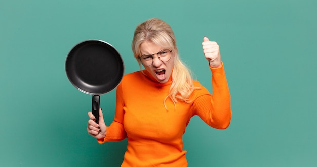 Blonde mooie vrouw die kok leert met een pan