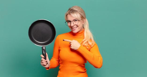 Blonde mooie vrouw die kok met een pan leert