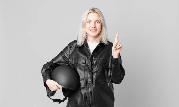 Blonde mooie vrouw die lacht en er vriendelijk uitziet, met nummer één. motorrijder concept