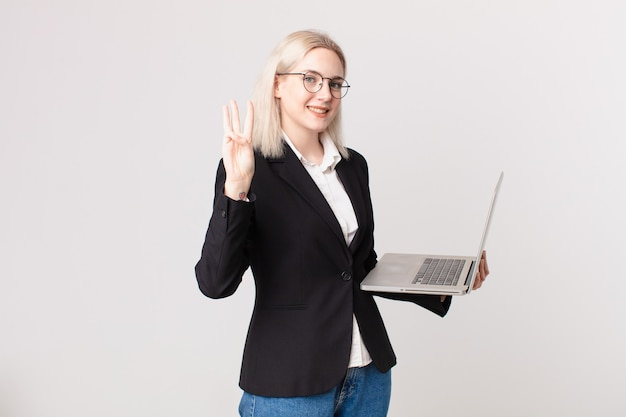 Blonde mooie vrouw die lacht en er vriendelijk uitziet, nummer drie toont en een laptop vasthoudt