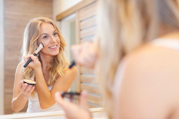 Blonde mooie vrouw die make-up voor spiegel doet