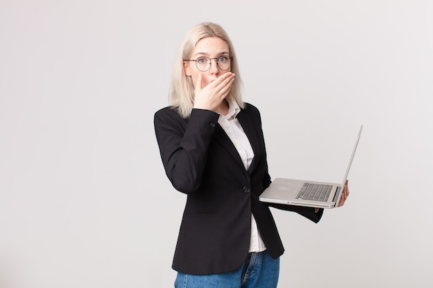 Blonde mooie vrouw die mond bedekt met handen met een geschokt en een laptop vasthoudt