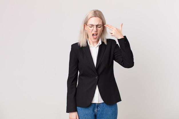 Blonde mooie vrouw die ongelukkig en gestrest kijkt, zelfmoordgebaar dat pistoolteken maakt. bedrijfsconcept
