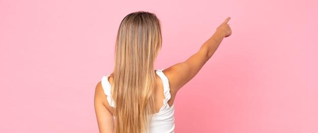 Blonde mooie vrouw die staat en wijst naar object op kopieerruimte, achteraanzicht
