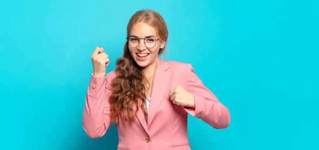 Blonde mooie vrouw die triomfantelijk schreeuwt, lacht en zich gelukkig en opgewonden voelt terwijl ze succes viert