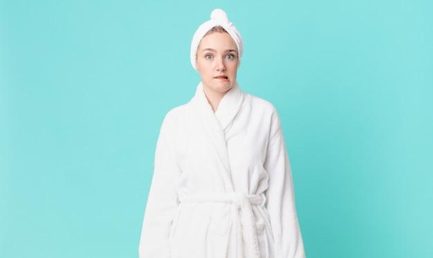 Blonde mooie vrouw die verbaasd en verward kijkt en een badjas draagt