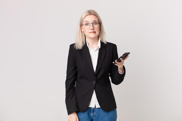 Blonde mooie vrouw die verbaasd en verward kijkt en een mobiele telefoon vasthoudt