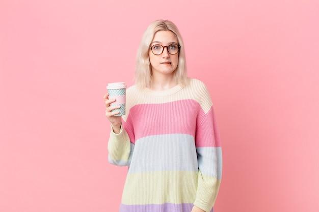 Blonde mooie vrouw die verbaasd en verward kijkt. koffie concept