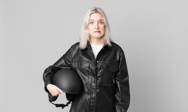 Blonde mooie vrouw die verbaasd en verward kijkt. motorrijder concept