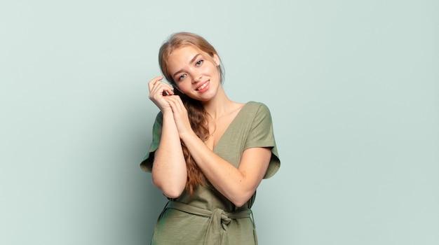 Blonde, mooie vrouw die verliefd voelt en er schattig, schattig en gelukkig uitziet, romantisch lacht met de handen naast het gezicht