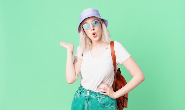 Blonde mooie vrouw die verrast en geschokt kijkt, met open mond terwijl ze een voorwerp vasthoudt. zomer concept