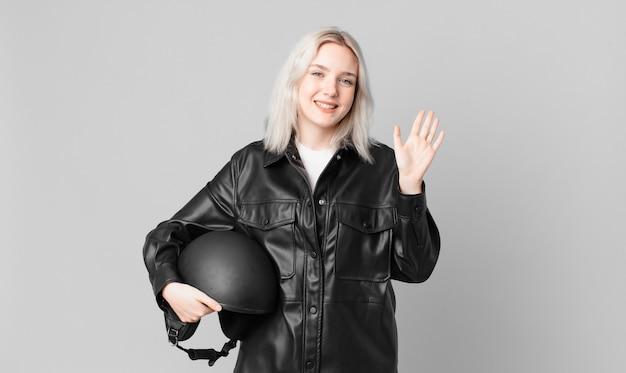 Blonde mooie vrouw die vrolijk lacht, met de hand zwaait, je verwelkomt en begroet. motorrijder concept