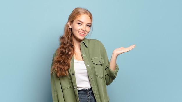 Blonde mooie vrouw die vrolijk lacht, zich gelukkig voelt en een concept in kopieerruimte toont met palm van hand