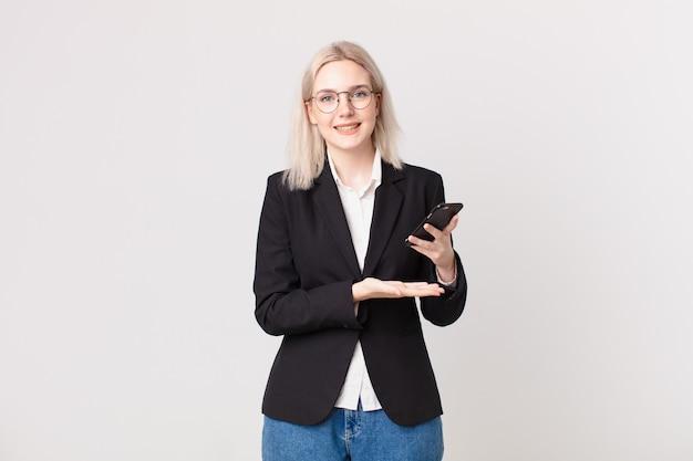 Blonde mooie vrouw die vrolijk lacht, zich gelukkig voelt en een concept toont en een mobiele telefoon vasthoudt