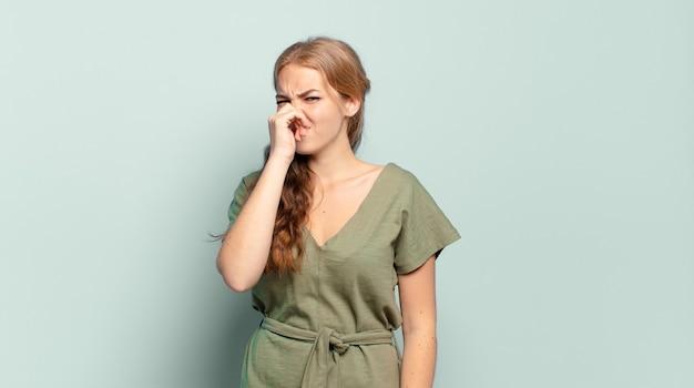 Blonde, mooie vrouw die walgt en neus vasthoudt om te voorkomen dat ze een vieze en onaangename stank ruikt