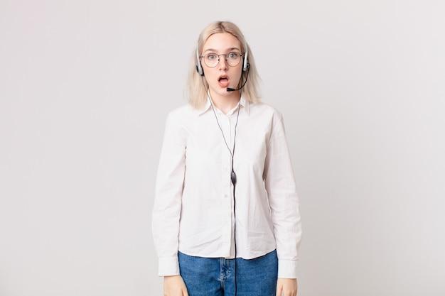Blonde mooie vrouw die zeer geschokt of verrast telemarketingconcept kijkt