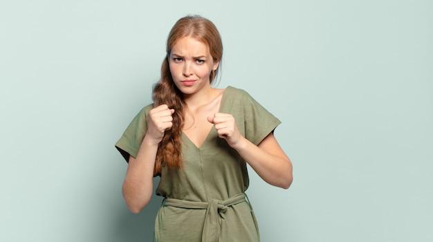 Blonde mooie vrouw die zelfverzekerd, boos, sterk en agressief kijkt, met vuisten klaar om te vechten in bokspositie