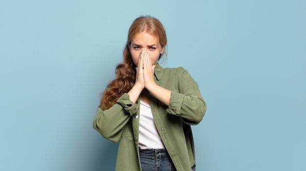 Blonde mooie vrouw die zich bezorgd, hoopvol en religieus voelt, trouw bidt met ingedrukte handpalmen, smekend om vergiffenis