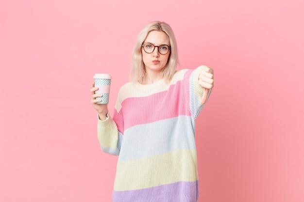 Blonde mooie vrouw die zich boos voelt en duimen naar beneden laat zien. koffie concept